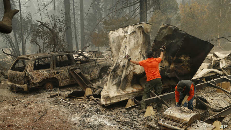 "Search and rescue workers search for human remains at a burned out trailer park from the ""Camp Fire,"" Nov. 13, 2018, in Paradise, California."