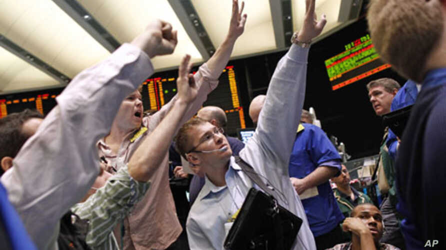 Traders work in the crude oil and natural gas options pit on the floor of the New York Mercantile Exchange in New York, (file photo April 25, 2011)