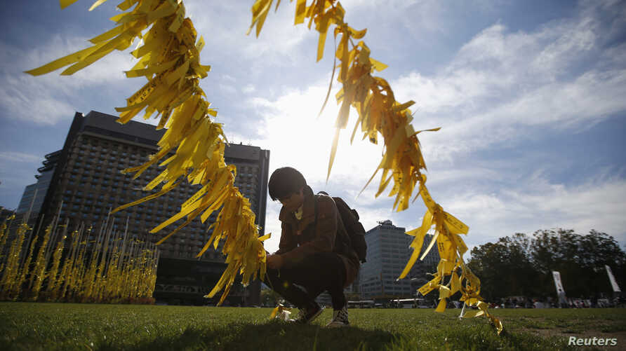 FILE - A man ties a yellow ribbon dedicated to victims onboard the sunken ferry Sewol, on a cable at Seoul City Hall Plaza, in Seoul.