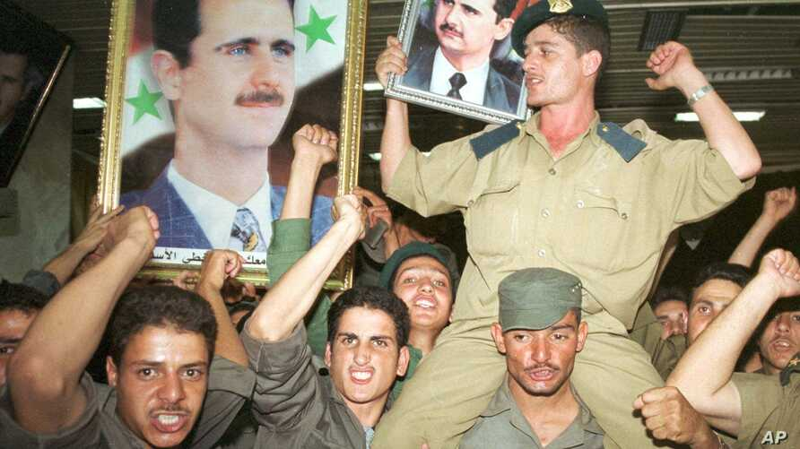 Syrian army soldiers wave portraits of Bashar Assad in Damascus, Syria, Monday, July 10, 2000. A month after President Hafez Assad's death, his son took a final step toward succeeding him Monday, standing as the only candidate in a nationwide preside
