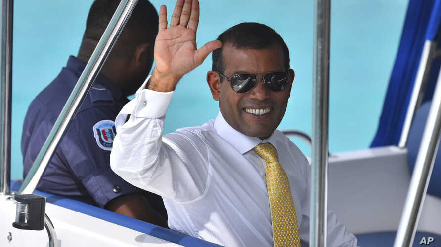 File - Maldives former President Mohamed Nasheed waves from a boat as he is taken back to Dhoonidhoo prison after a court dismissed his appeal against his arrest in Male, Maldives, March 2015.