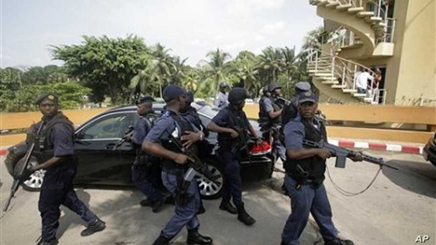 South African police officers stand guard around a car transporting President Jacob Zuma, as he leaves following a meeting with Ivory Coast's internationally-recognized president, Alassane Ouattara, at the Golf Hotel in Abidjan, Ivory Coast, February