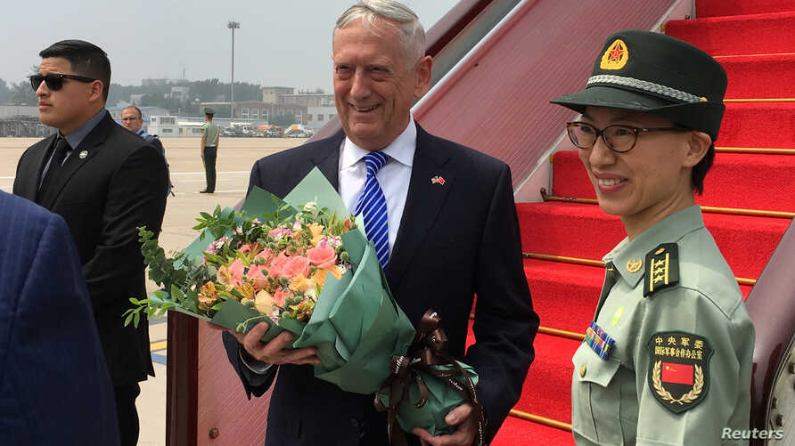 U.S. Defense Secretary Jim Mattis receives a bouquet upon arrival at an airport in Beijing, China, June 26, 2018.