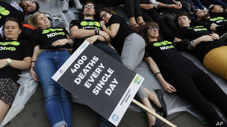 FILE - Supporters stage a 'Die-In' to mark World Hepatitis Day at Piccadilly Circus in London.