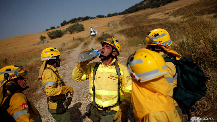 A firefighter drinks water after extinguishing a forest fire during a heatwave in Benaojan, Spain, July 12, 2017. A new fire burns in a national park.