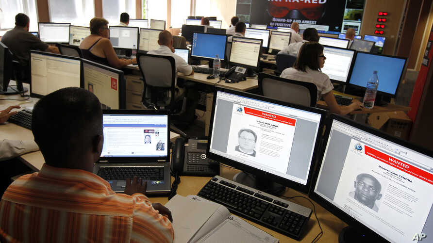 Interpol employees work in the control room of the Infra-Red operation in Lyon, central France, July 5, 2010.