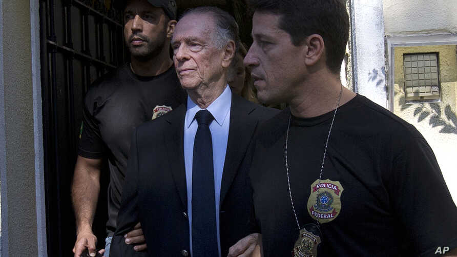 Carlos Nuzman, President of the Brazilian Olympic Committee, center, is escorted by federal police officers after being taken into custody at his home, in Rio de Janeiro, Brazil, Oct. 5, 2017.