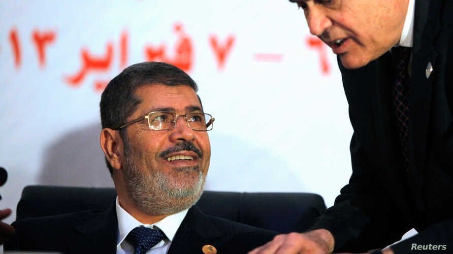 Egyptian President Mohammed Morsi listens to his Foreign Minister Mohammed Kamel Amr during the opening of the 12th summit of the Organization of Islamic Cooperation in Cairo, Egypt, February 6, 2013.