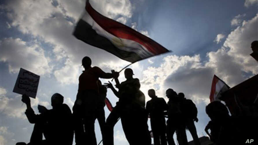 Anti-government protesters hold an Egyptian flag during demonstrations in Tahrir Square in downtown Cairo, Egypt, Feb. 8, 2011