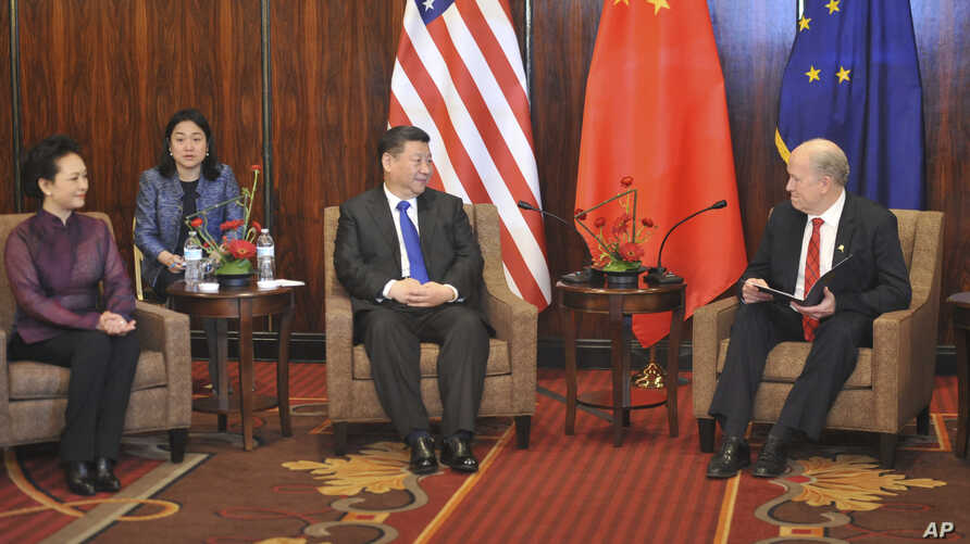 Chinese President  Xi Jinping, center, listens to Alaska Governor Bill Walker at a meeting Friday April 7, 2017, in Anchorage, Alaska. At left is Chinese first lady Peng Liyuan. Xi requested time with Gov. Bill Walker Friday night as the Chinese dele