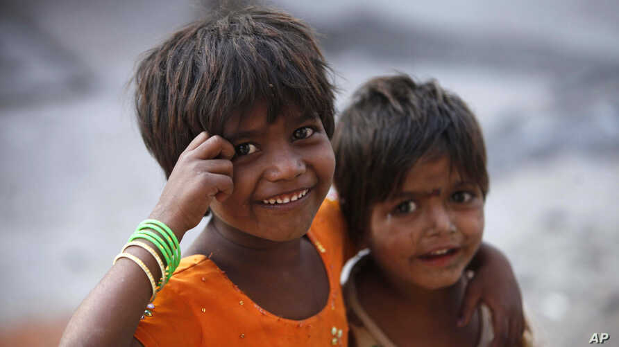 Two Indian girls react to the camera as they play on a street outside their roadside shanty, on International Day of the Girl Child in Hyderabad, India, Oct. 11, 2012.