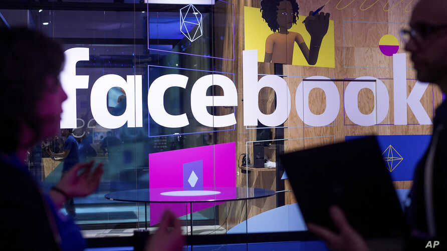 File - In this April 18, 2017, photo, workers stand in front of a demo booth at Facebook's annual F8 developer conference in San Jose, California.
