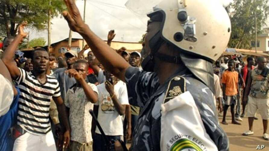 Opposition activists chant slogans towards a police officer during demonstrations in Lome, 09 March 2010