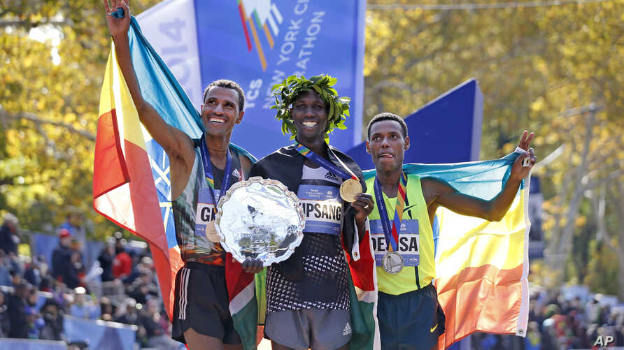 Men's winner Wilson Kipsang, center, is joined by second-place finisher Lelisa Desisa Benti, of the United States, left, and third place finisher Gebre Gebremariam, of Ethiopia, after the 44th annual New York City Marathon in New York, Nov. 2, 2014. ...