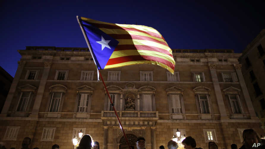 A demonstrator waves a pro-independence Catalan flag outside the Palau Generalitat, during a protest against the decision of a judge to jail ex-members of the Catalan government, in Barcelona, Spain, Nov. 3, 2017.