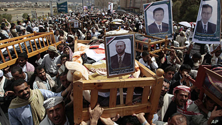 Anti-government protesters carry the bodies of fighters loyal to opposition tribal chief Sheikh Sadiq al-Ahmar, who were killed during clashes with security forces, during a mass funeral in Sana'a, June 3, 2011