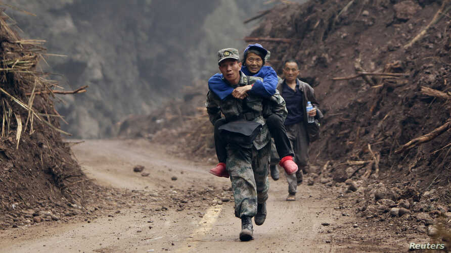Zhang Bin, a Chinese People's Liberation Army soldier, carries a 60-year-old survivor as he runs down a stretch of the road to Lingguan township which was recently cleared of debris from landslides caused by Saturday's earthquake, in Baoxing county i