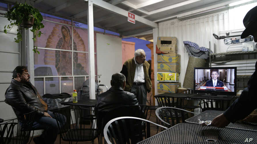 A group of Hispanic people watch a television broadcast of President Barack Obama's speech on immigration at a Mexican restaurant, Nov. 20, 2014, in Los Angeles.