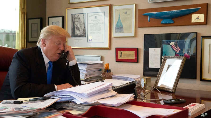 Republican presidential candidate Donald Trump takes a telephone call from his daughter Ivanka during an interview with The Associated Press in his office at Trump Tower, Tuesday, May 10, 2016, in New York.