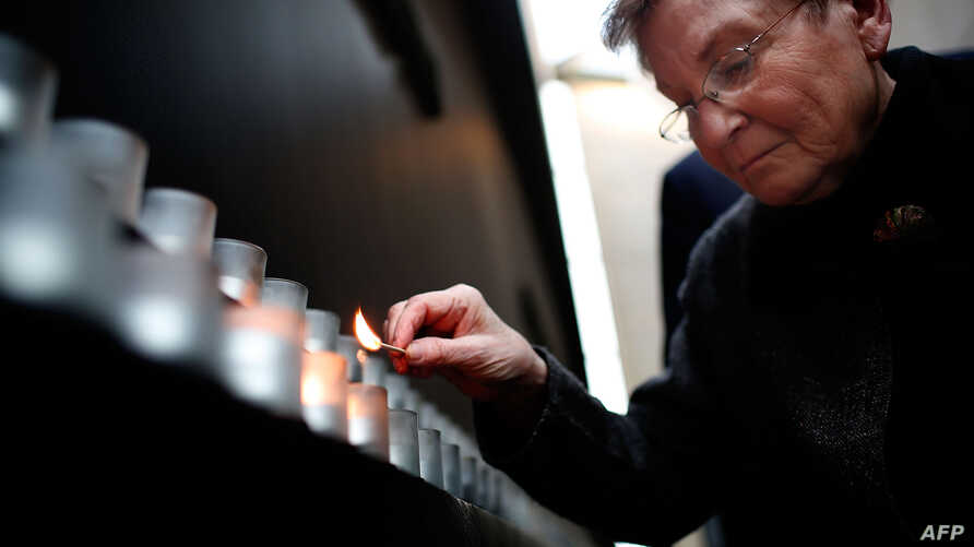 Holocaust survivor Josiane Traum lights a memorial candle during an International Holocaust Remembrance Day Commemoration at the United States Holocaust Memorial Museum, Jan. 27, 2017 in Washington, D.C.