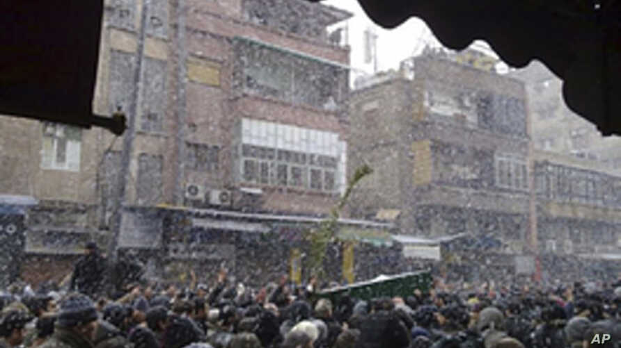Anti-government protesters attend the funerals, in snowy weather, of those killed during clashes with government troops in earlier protests against Syria's President Bashar al-Assad in Damascus, February 18, 2012.