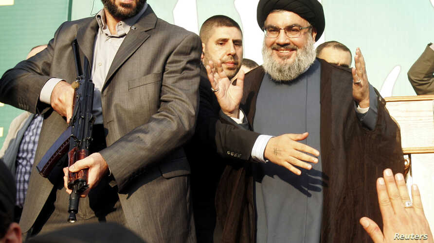 Lebanon's Hezbollah leader Sayyed Hassan Nasrallah (R), escorted by his bodyguards, makes a rare public appearance as he greets his supporters at an anti-U.S. protest in Beirut's southern suburbs September 17, 2012. Nasrallah made a rare public appea