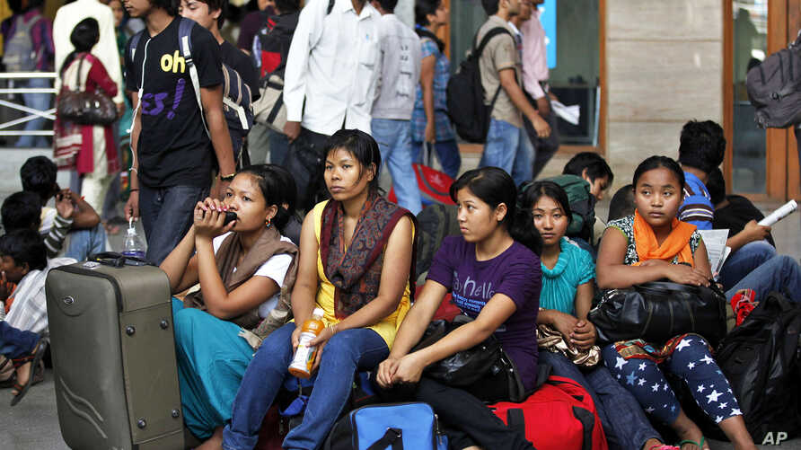 Women from India's northeastern states wait with their baggage to board trains home, at a railway station in Bangalore, India, August 16, 2012.