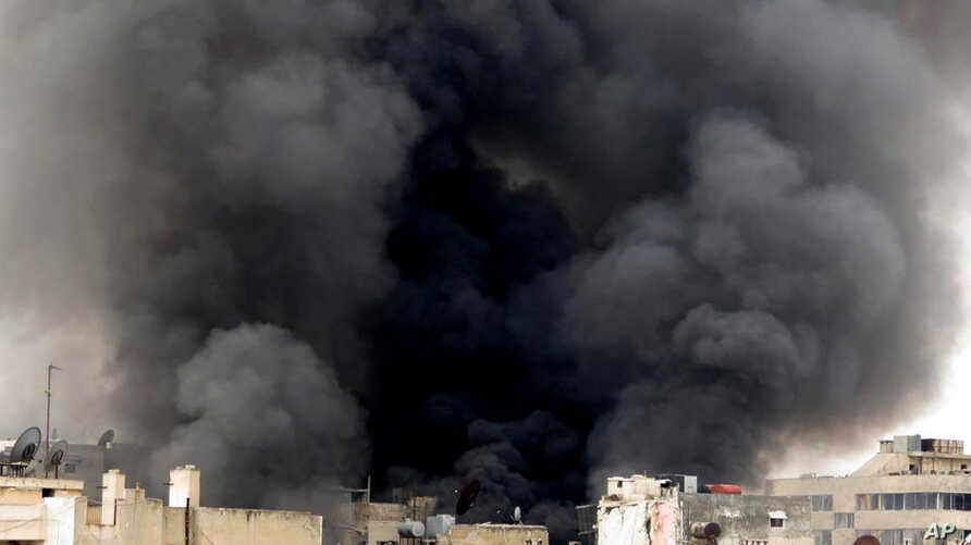 In this Tuesday March 19, 2013, citizen journalism image provided by Aleppo Media Center AMC which has been authenticated based on its contents and other AP reporting, black smoke rise from buildings due to government forces shelling, in Aleppo, Syri