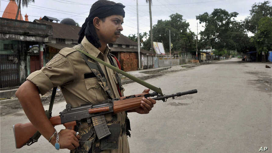 An Indian armed security man stands guard in a riot-hit locality in Kokrajhar, India, July 24, 2012.