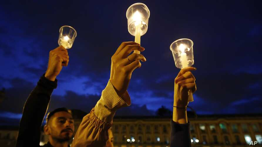 FILE - Demonstrators light candles during a candlelight vigil for slain activists in Bogota, Colombia, July 6, 2018.