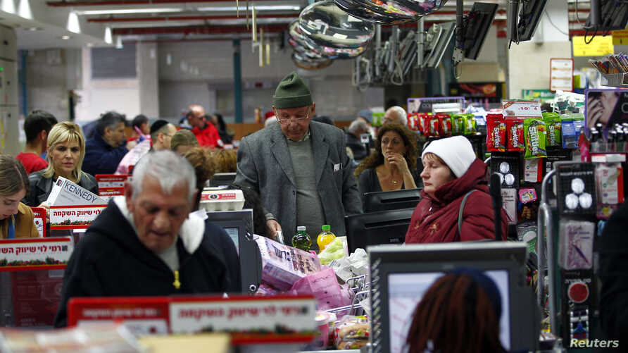 People stand at the checkout line in a supermarket in Jerusalem, Jan. 6, 2015.