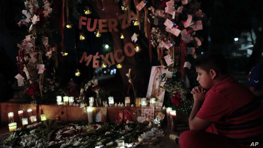 A child prays in front a street altar near a collapsed building in Amsterdam Street in the Condesa neighborhood of Mexico City, Sept. 24, 2017.