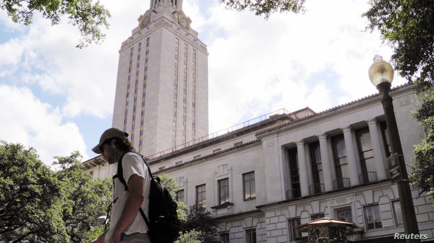 FILE - A student walks past the clock tower at the University of Texas in Austin, Texas, June 23, 2016. On Monday, the state began allowing concealed handguns on public university campuses.