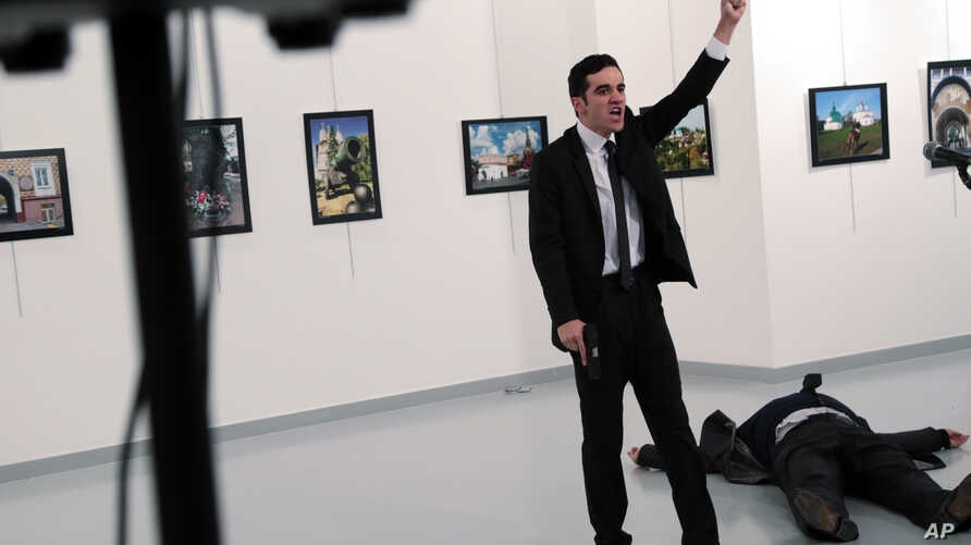 A man identified as Mevlut Mert Altintas shouts after shooting Andrei Karlov, the Russian Ambassador to Turkey, at a photo gallery in Ankara, Turkey, Dec. 19, 2016.