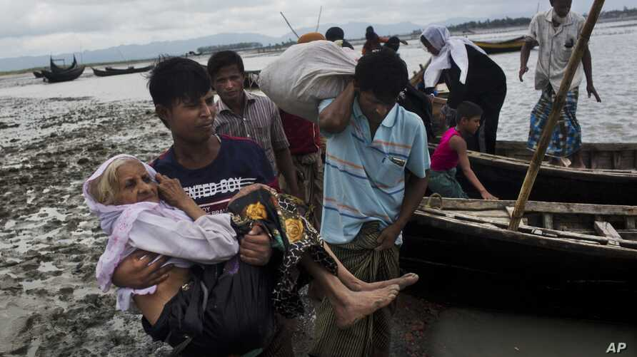 A Rohingya ethnic minority from Myanmar carries an elderly woman as they alight from a local boat on which they crossed a river, after crossing over to the Bangladesh side of the border near Cox's Bazar's Dakhinpara area, Saturday, Sept. 2, 2017.
