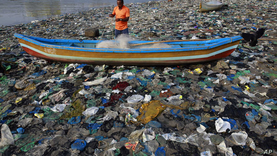 A fisherman prepares his net on the shores of the Arabian Sea, littered with plastic bags, in Mumbai, India, Thursday, Oct. 1, 2015.
