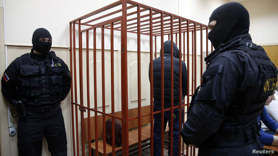 FILE - A defendant stands inside a special cage as he attends a court hearing in Sakhalin, Russia, March 4, 2015. The number of people imprisoned in Russia on extremism-related charges jumped from 137 in 2011 to 414 in 2015, according to an independe