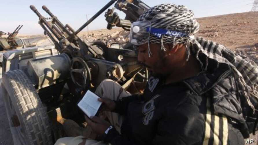 An anti-Gaddafi fighter reads the Koran at a checkpoint north of Bani Walid. (file photo)