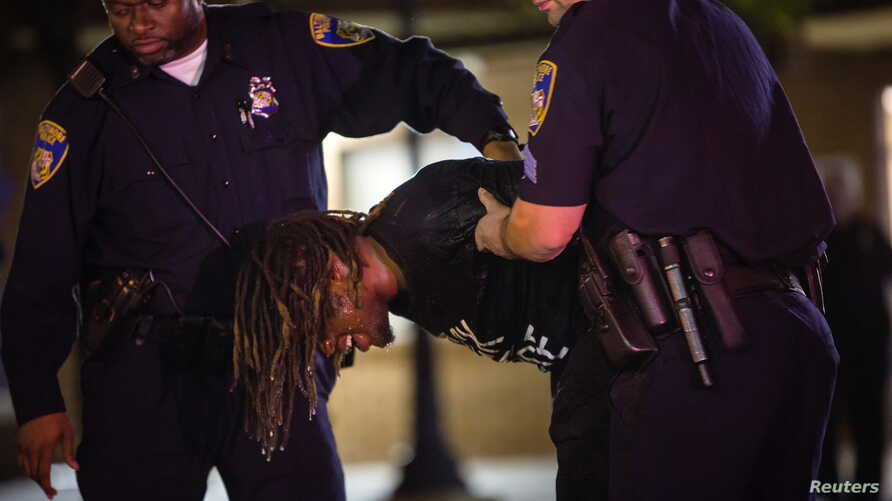 A demonstrator is taken into custody after defying a citywide curfew in Baltimore, Maryland, May 2, 2015.