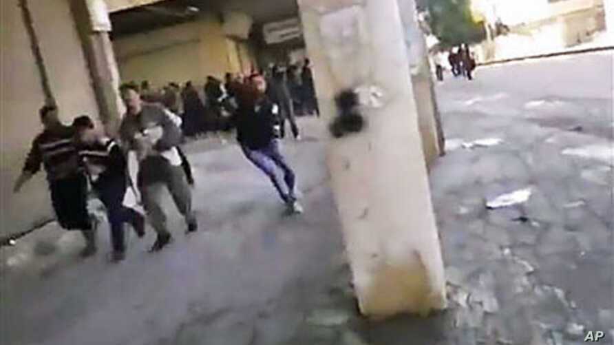This image from amateur video purports to shows Syrian protesters running from gunfire in Hama, Syria, December 28, 2011.