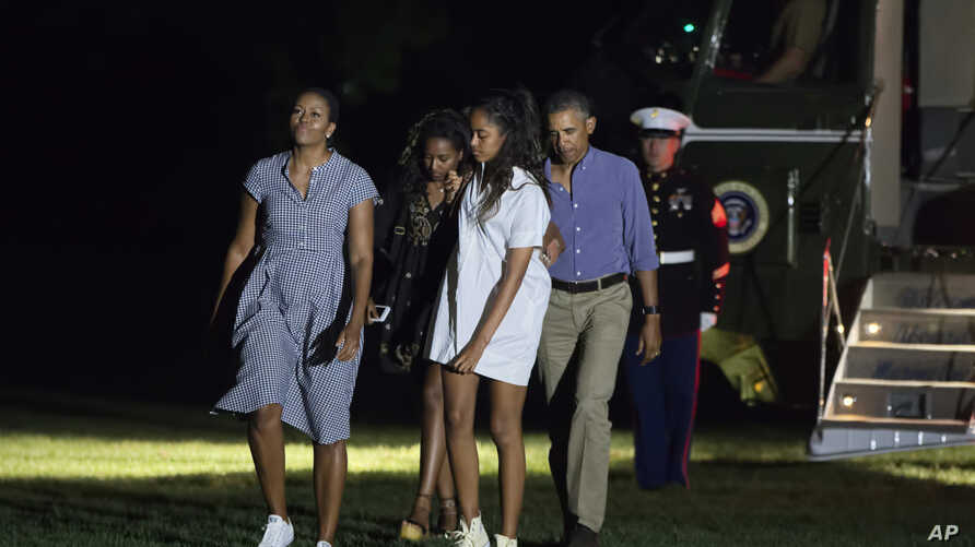 First lady Michelle Obama, from left, daughters Sasha Obama, Malia Obama and President Barack Obama return from a 16-day vacation to Martha's Vineyard, Mass., arriving at the White House in Washington, Sunday, Aug. 21, 2016.