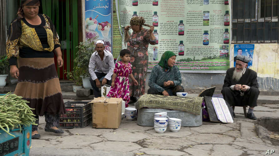 FILE - In this photo taken July 17, 2014,  Uighur residents gather at a road side stall in the city of Aksu in western China's Xinjiang province.
