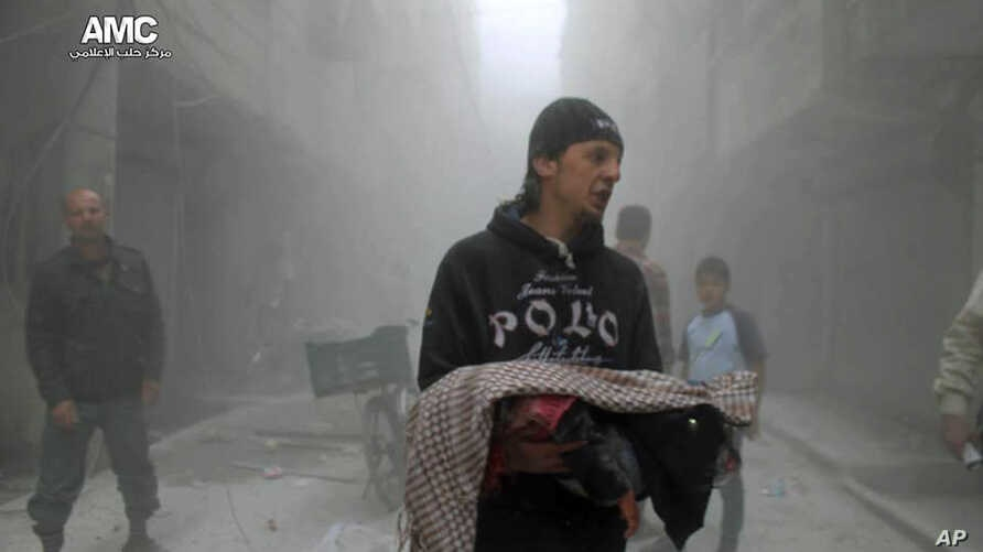 This photo provided by the anti-government activist group Aleppo Media Center (AMC), which has been authenticated based on its contents and other AP reporting, shows a Syrian man carrying the body of a child killed by a government forces airstrike in