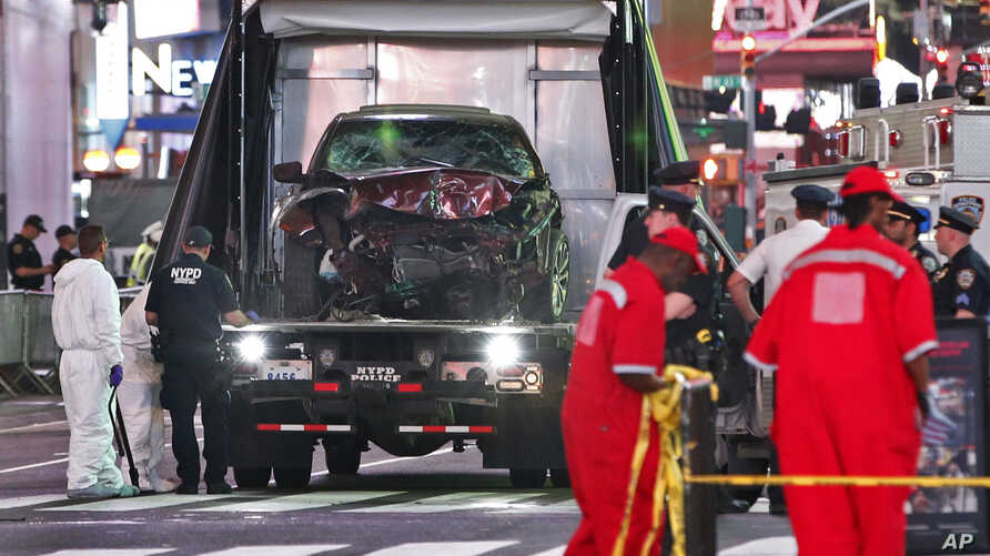 The car driven by a man who steered his car onto a busy Times Square sidewalk, killing a teenager and injuring nearly two dozen others, is removed by police and investigators from the crime scene area, May 18, 2017, in New York.