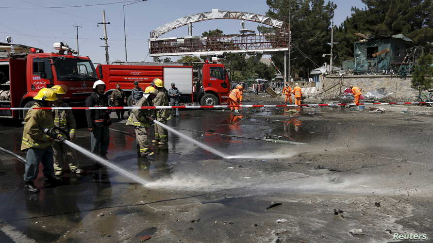 Afghan workers clear debris from the site of a car bomb blast at the entrance gate to the Kabul airport, Afghanistan, Aug. 10, 2015.