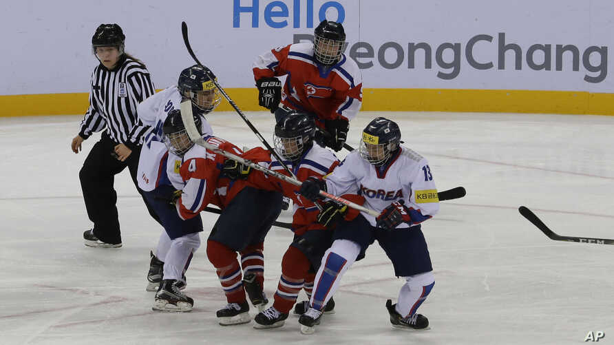 FILE - South Korea, wearing white uniforms, and North Korean players compete during their IIHF Ice Hockey Women's World Championship Division II Group A game in Gangneung, South Korea, April 6, 2017.