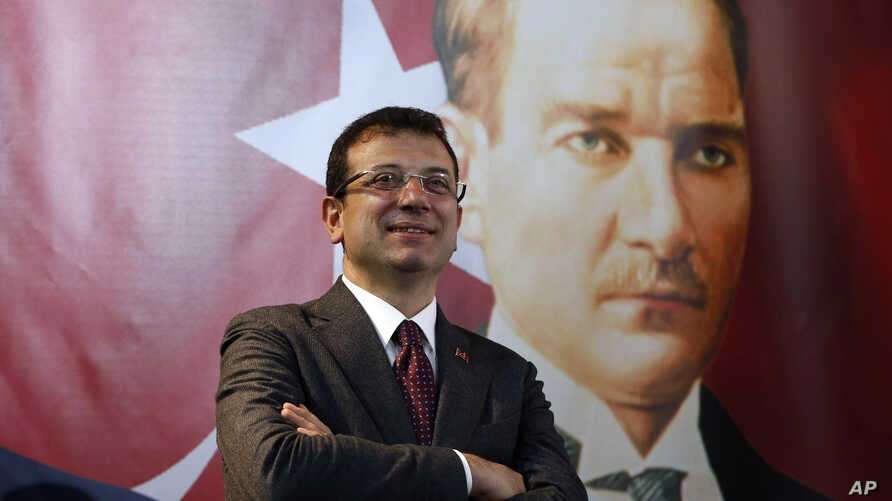 Backdropped by a poster of modern Turkey's founder Mustafa Kemal Ataturk, right, Ekrem Imamoglu, the opposition, Republican People's Party's (CHP) mayoral candidate in Istanbul, poses following an interview in Istanbul, April 4, 2019.