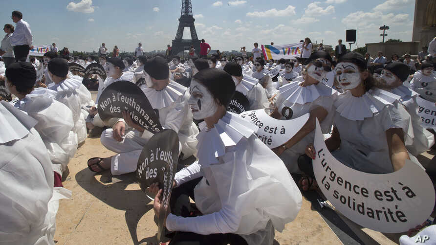 """Demonstrators dressed as mime artists hold placards that read """"no to the euthanasia of elderly people, solidarity is urgent,"""" at Trocadero plaza in Paris, France, June 24, 2014."""