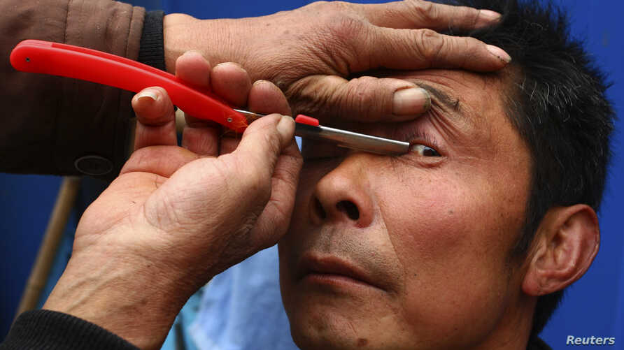 FILE - A barber uses a razor to clean the eyelids of his customer, as a part of his hair shaving service, at a residential area in Suining, Sichuan province, Feb. 23, 2012.