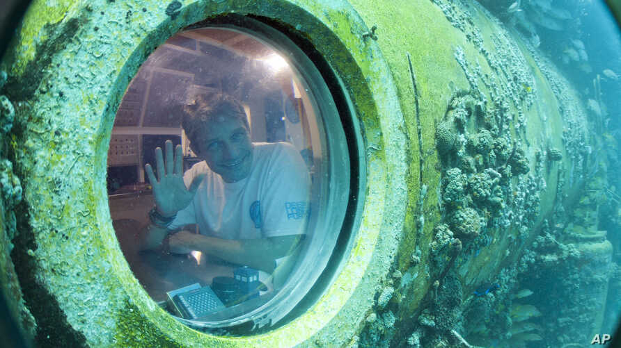 Fabien Cousteau waves from inside Aquarius Reef Base, a laboratory 63 feet below the surface in the waters off Key Largo, in the Florida Keys National Marine Sanctuary, June 24, 2014.